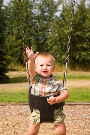 A portrait of a cute one year old baby boy on a swing. Stock Photo - 5489262