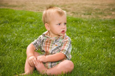 A portrait of a cute one year old baby boy at a park. Imagens