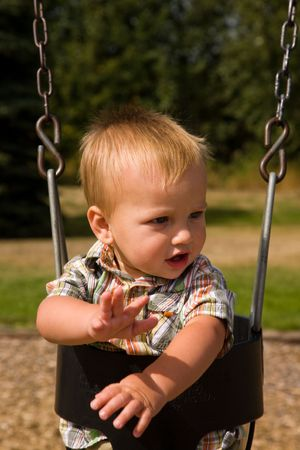 A portrait of a cute one year old baby boy on a swing.