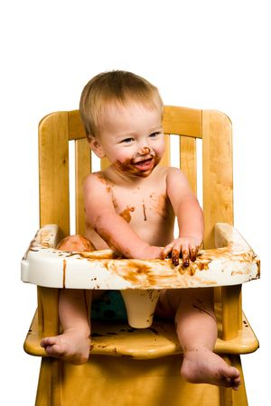 A portrait of a messy baby boy isolated eating chocolate.