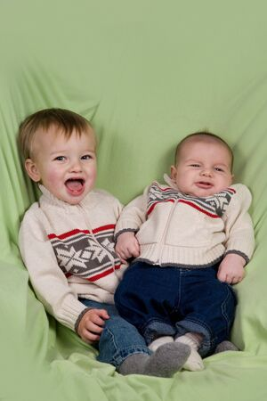 A portrait of two baby boys (cousins) in winter clothes. Stock Photo