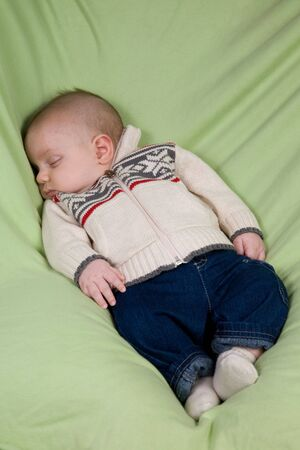 A portrait of a newborn baby boy sleeping in winter clothes. photo