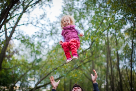 tosses: Healthy father tosses his little smily daughter in the park Stock Photo