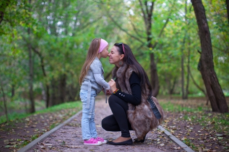 Cute little girl kissing her mother s nose photo