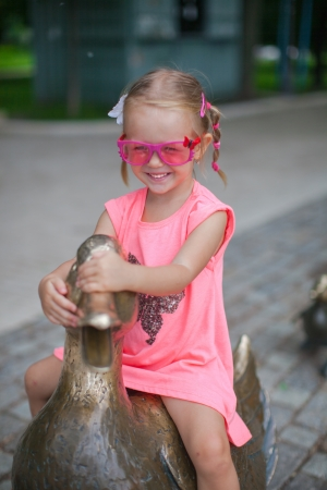 little girl astride on a duck figure of iron and having fun photo