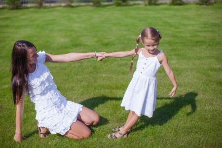 Young happy mother and her daughter having fun in the yard photo