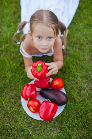Little girl with pigtails in a garden with a plate of vegetables photo