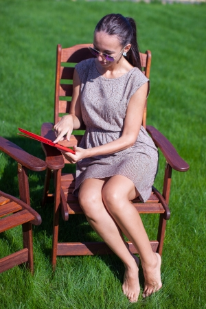 Young woman in sunglasses on chair outdoor looking at laptop photo