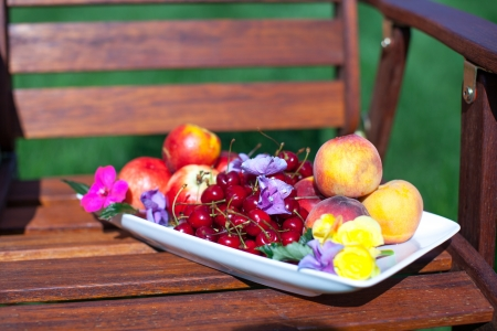 Plate with fresh fruits and flowers on wooden chairs photo