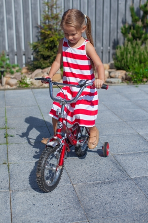 Little cute girl rides a bicycle in the dress in the yard photo