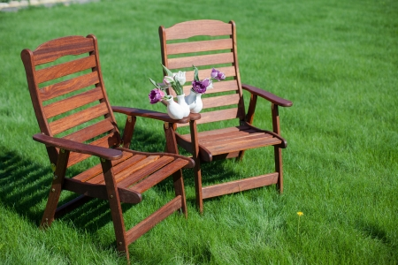 two wood chairs on the grass with vase of flowers on them photo