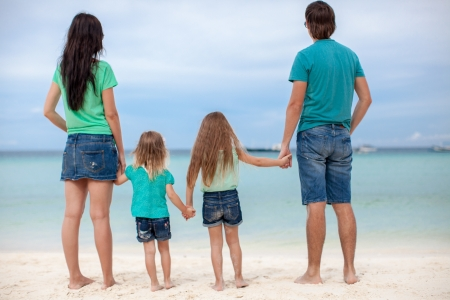 Back view of beautiful family with two kids at exotic beach photo