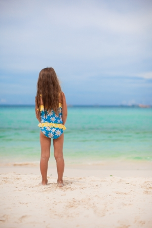 Beautiful little girl alone looks at the sea on the white beach photo