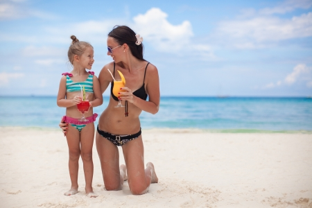 Happy mother and her adorable little daughter with juice at tropical beach photo