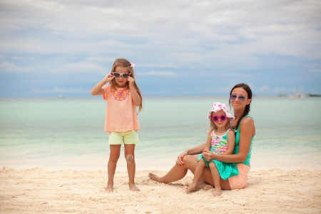 Bright mother and two her kids at exotic beach on sunny day photo