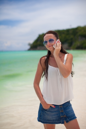young beautiful woman on the beach talking on her phone photo