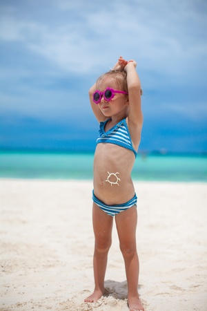 little girl on her stomach painted a smile by sun cream photo