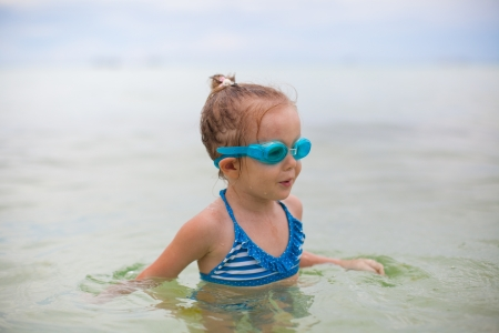 Little girl with glasses for swimming swims and dives in the sea photo