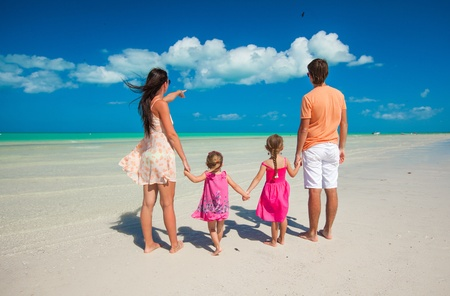 Back view family of four on caribbean beach vacation photo