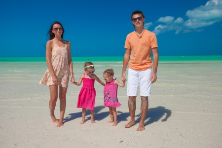 Young nice family with two kids walking at beach photo