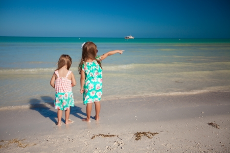 Back view of two little cute fashion sisters on the beach photo