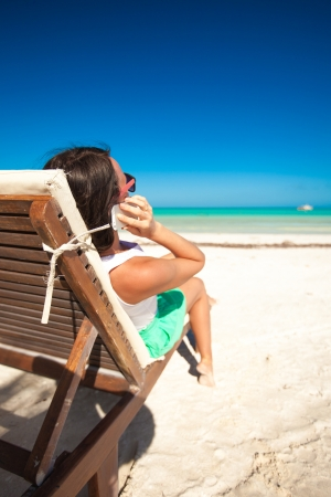 Young woman talking on the phone while sitting on a beach lounger Stock Photo