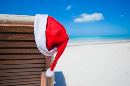 Close-up santa hat on chair longue on tropical caribbean beach photo