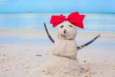 Little sandy snowman with bow on a sandy Caribbean beach photo