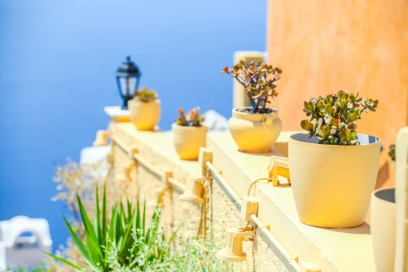 Traditional greek details  colorful flowers with pots, lantern and caldera sea in background photo