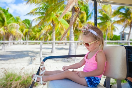 little cute girl sitting in a golf car in a tropical grove photo