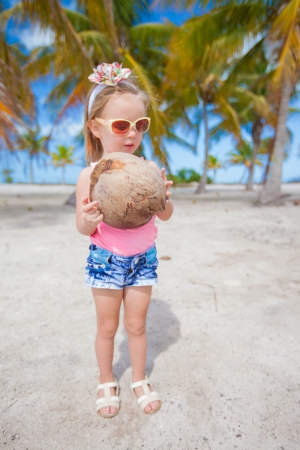 little cute girl with a big coconut in palm grove in exotic country photo