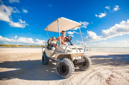 Dad with his two daughters driving golf cart at tropical beach photo