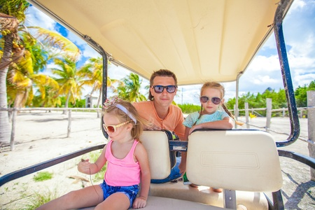 Young father and his little daughters inside golf cart at tropical country photo