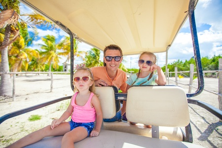 Back view of father and his little daughters inside golf cart at tropical country photo