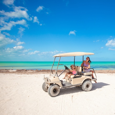 two daughters and their mother driving golf cart at tropical beach photo