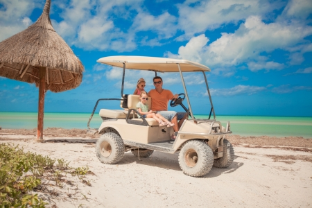 Dad and his two daughters driving golf cart on a tropical beach photo
