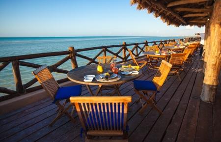 Summer empty open air restaraunt near sea at sunset photo