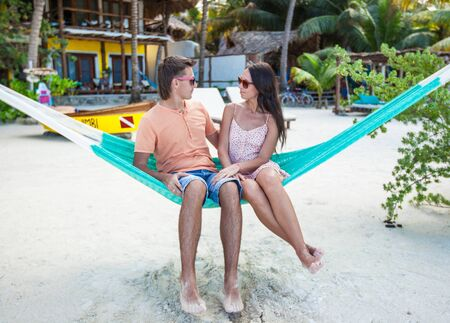 Young Couple Sitting In Hammock On The Beach And Looking Each Other photo