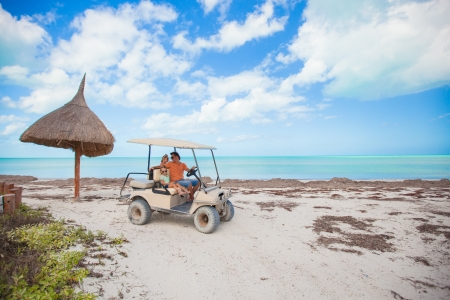 General view golf car with family inside on an exotic beach photo