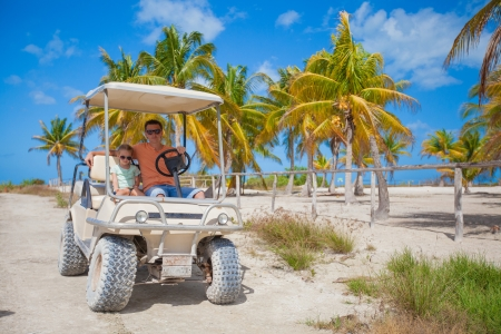 Dad and his two daughters driving golf cart at tropical country photo