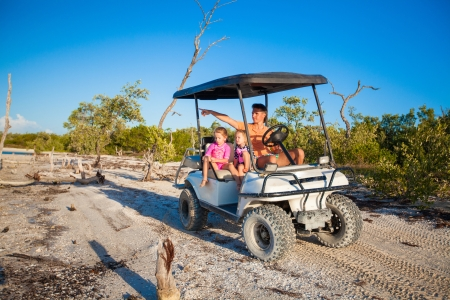 Dad and his two daughters driving golf cart at tropical beach photo