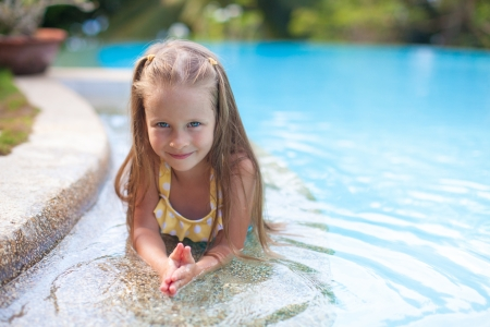 Adorable girl in the swimming pool looks at camera photo
