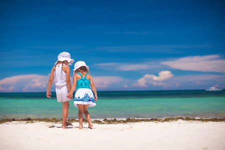 youngbaby: Back view of two little sisters looking at the sea on the white beach