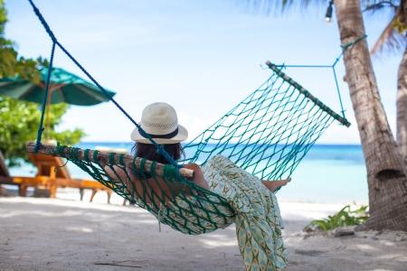 Woman in hat lying in hammock in trees shadow on a beach Stock Photo