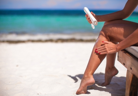 young woman apply cream on her smooth tanned legs on tropical beac