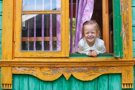 Adorable little girl looks out the window rural house and laughs photo