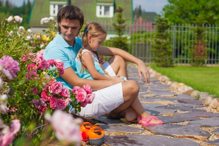 Little cute girl and father relaxing in their garden photo