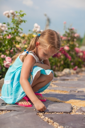 Cute small girl drawing on the sidewalk with chalk in the yard photo