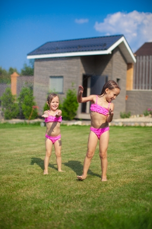 Two little sisters frolicing and splashing in their yard photo