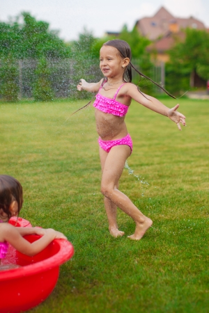 Adorable little girl in a swimsuit playing and splashing in the yard photo